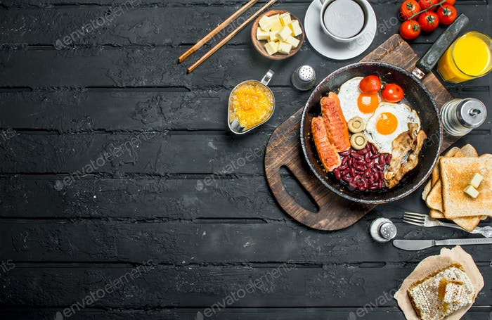 Traditional English Breakfast with fried eggs, sausages and aromatic coffee.