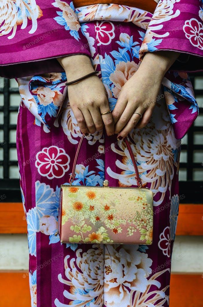 Nahaufnahme der Frau in Kimono hält Geldbörse