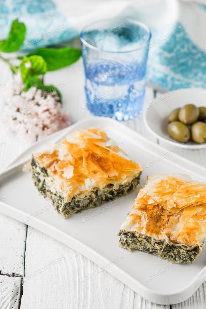 Griechische Kuchen spanakopita auf der weißen Platte mit Zubehör vertikal