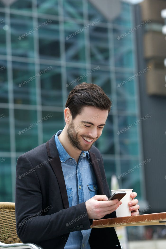 Man smiling with phone at outdoors cafe