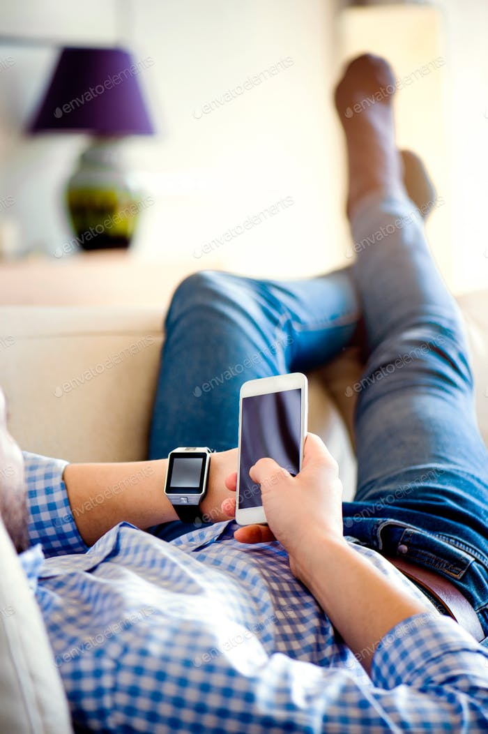Man lying on sofa using smartphone and smart watch