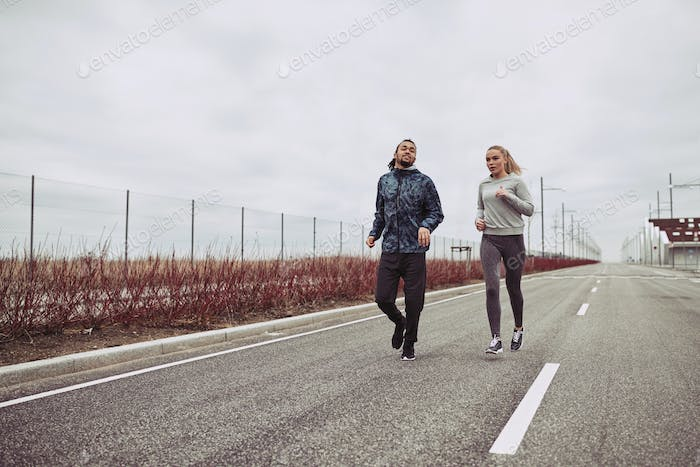 Diverse young couple in sportswear jogging on a country road