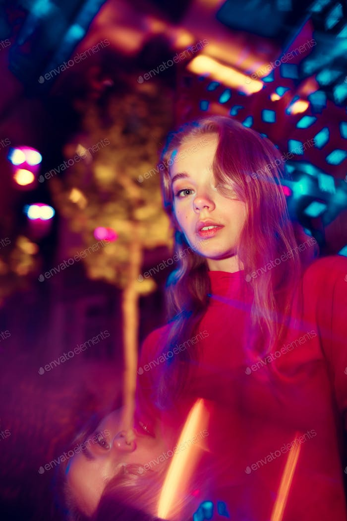 Cinematic portrait of handsome young woman in neon lighted room, stylish musician