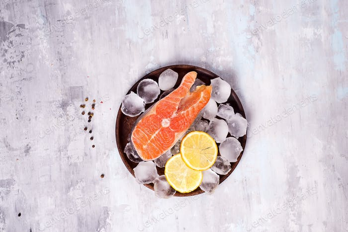 Salmon steaks on ice with lemon slice on wooden plate