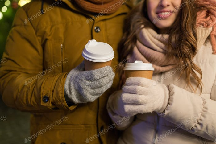 close up of happy couple with coffee at christmas