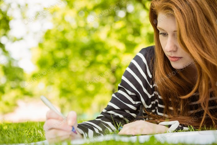Young female college student doing homework in the park