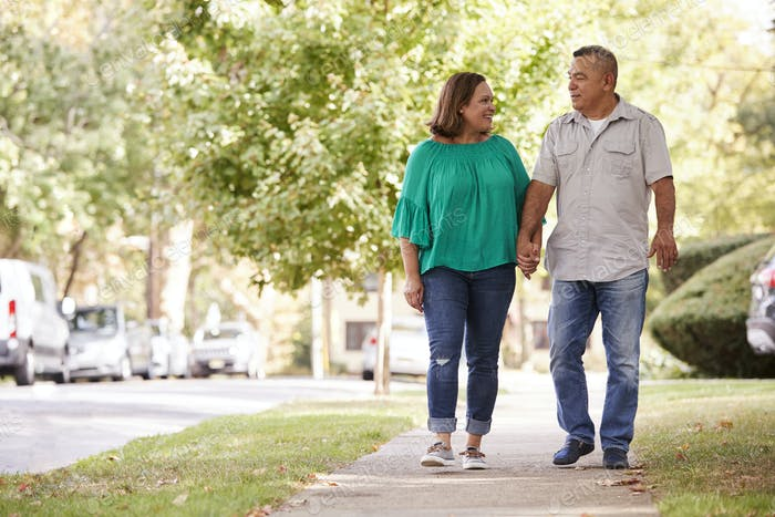 Senior Couple Walking Along Suburban Street Holding Hands