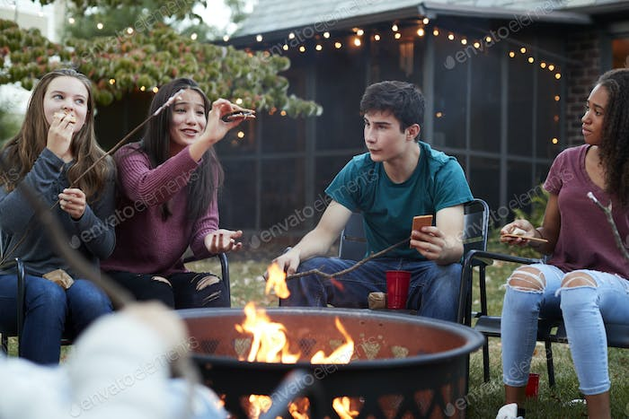 Teenage friends eating somores around a firepit
