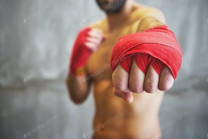 Schuss von eingewickelten Händen mit rotem Boxband des jungen Boxerkampfes
