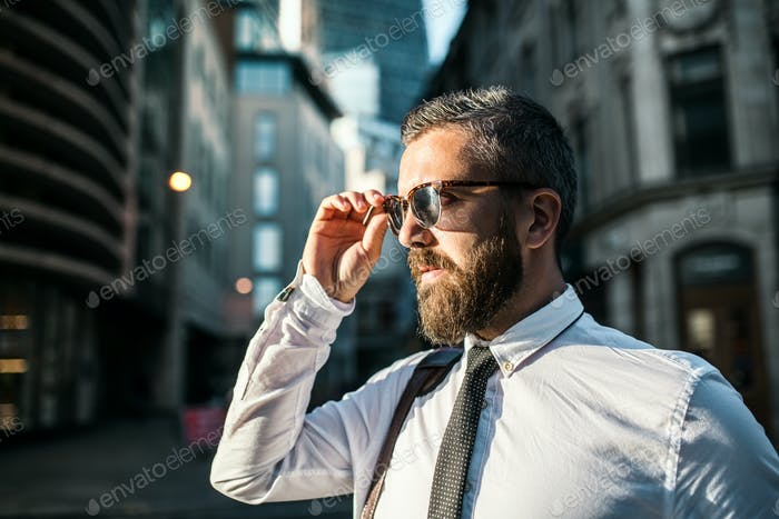 Hipster businessman with sunglasses standing on the street in city. Copy space.