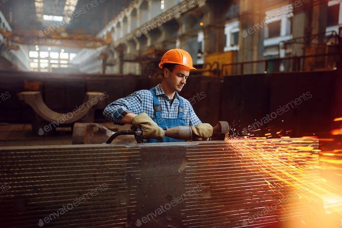 Worker in helmet works with metal workpieces