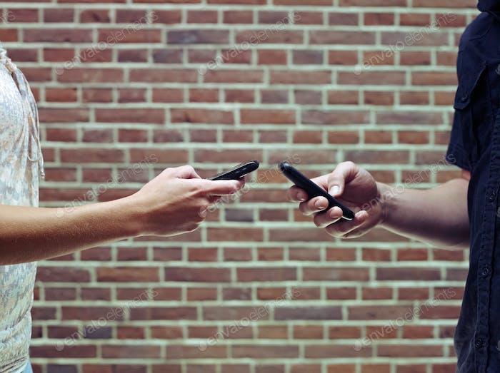 Mann und Frau mit Handys, um Dateien und Kontakte zu teilen