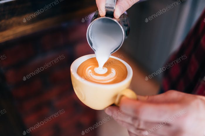 Barista using coffee machine preparing fresh coffee with latte foam at coffee shop and restaurant,
