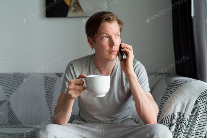 Young handsome man holding coffee and talking on the phone at home