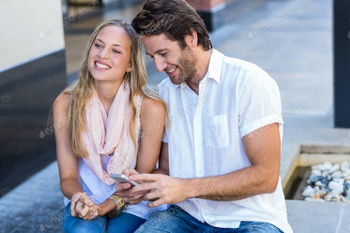 Smiling couple sitting and holding smartphone at shopping mall