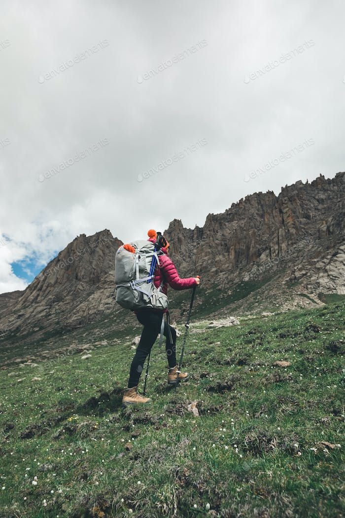 Backpacking woman ascent on high altitude mountains
