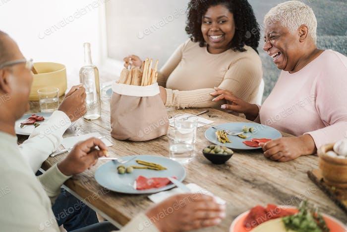Feliz familia negra comiendo el almuerzo en casa