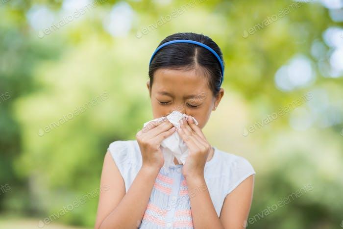Mädchen blasen ihre Nase mit Taschentuch beim Niesen