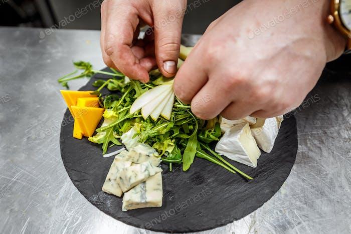 Chef garnishing cheese platter