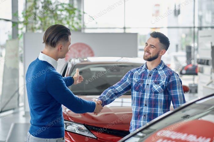 Zwei Männer stehen im Salon zwischen Autos und Händeschütteln