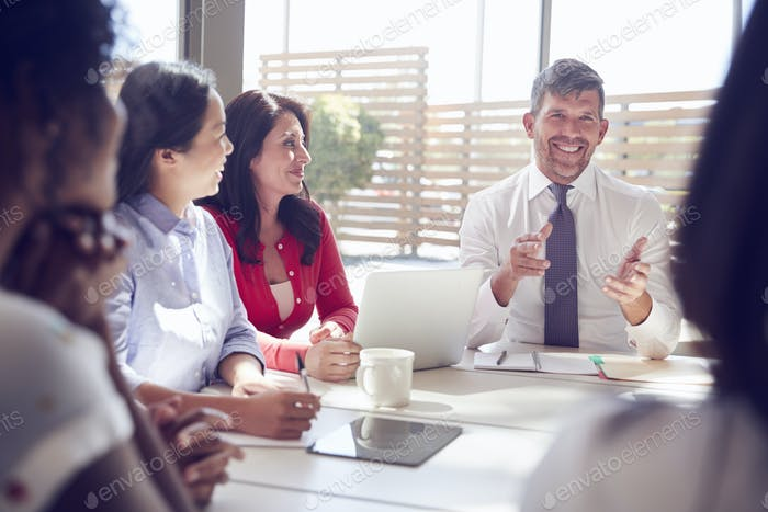 Thumbnail for Smiling businessman talking to colleagues in a  meeting room