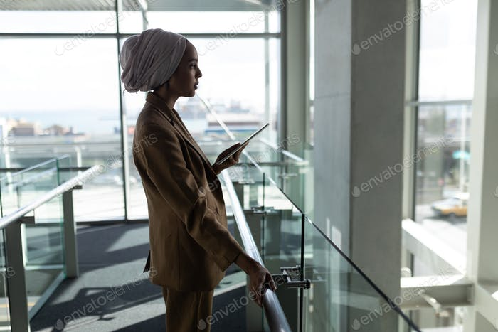 Side view of businesswoman using digital tablet in the office