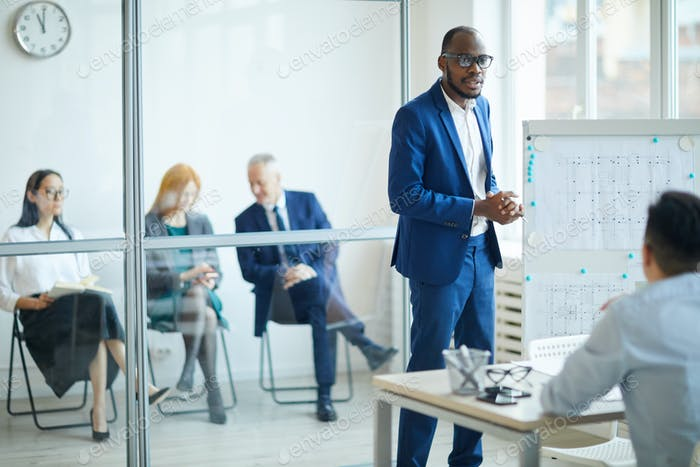 African Man Pitching Ideas to Management
