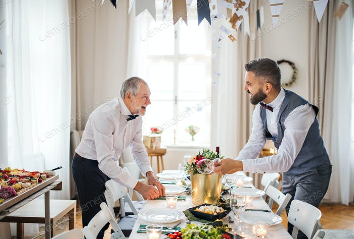 Two men with bows setting a table for an indoor party, talking.