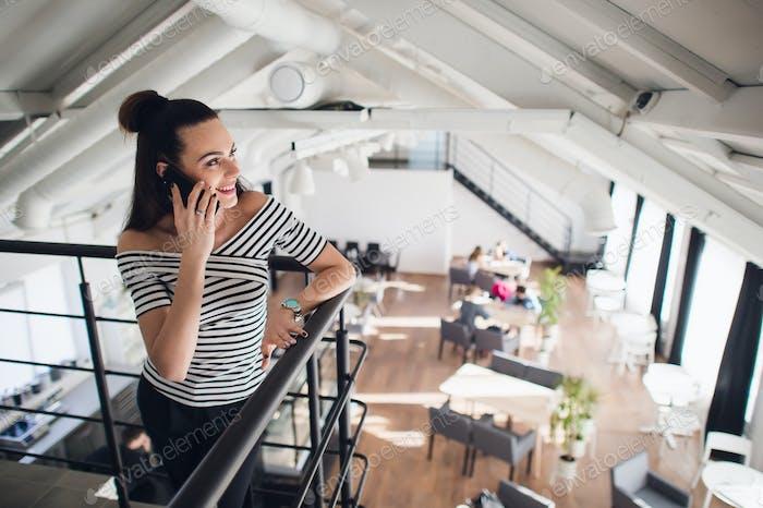 Junge Frau telefoniert mit einem Freund und lächelnd beim Wegschauen. Verschwommenes Café, große Fenster