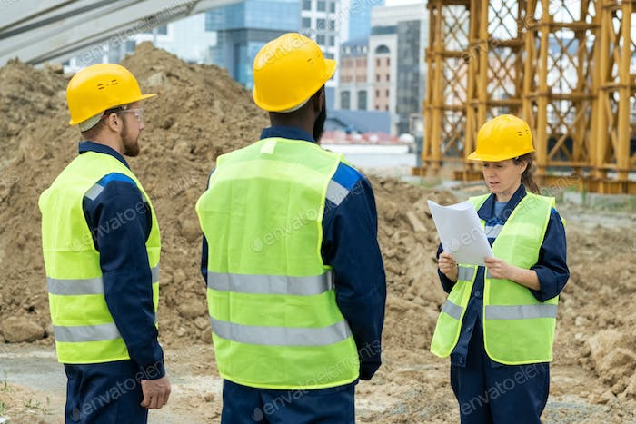 Two intercultural male builders listening to their female colleague with paper