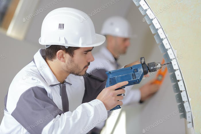 construction worker with tools and drill renovating house