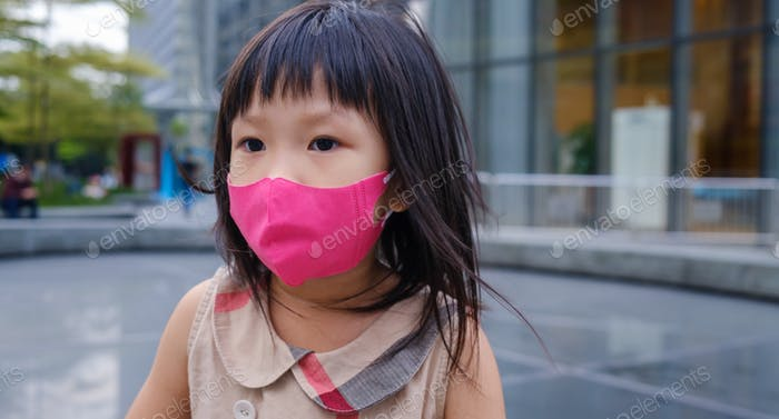 Asian little girl resting on the street with a mask