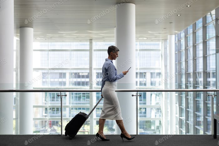 Side view of mature Caucasian businesswoman using mobile phone while walking in modern office