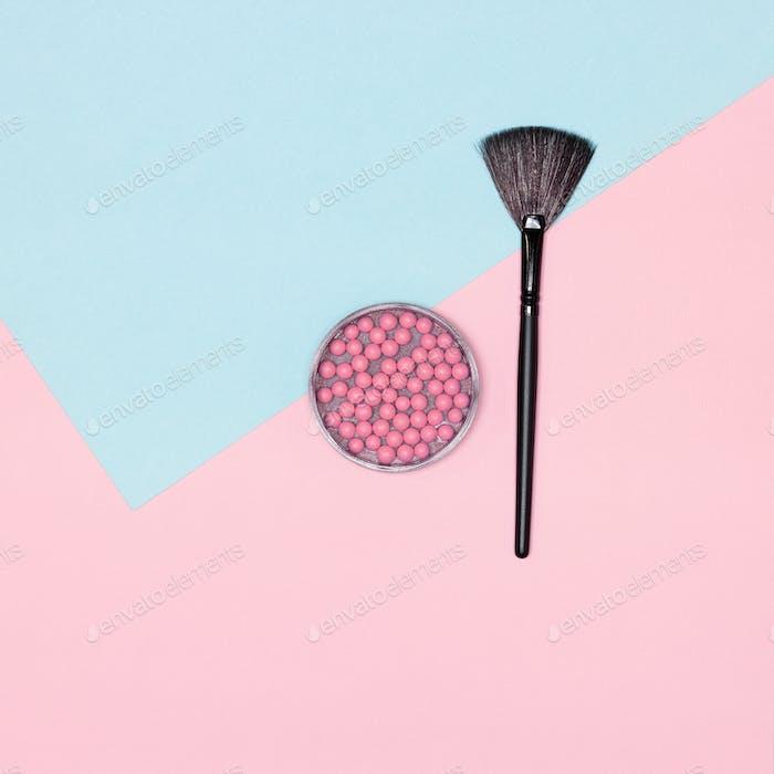 Румяна для макияжа с кистью для макияжа на розовом и синем фоне