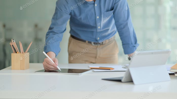 Professional designer is working on a tablet to design his future project in a comfortable office.