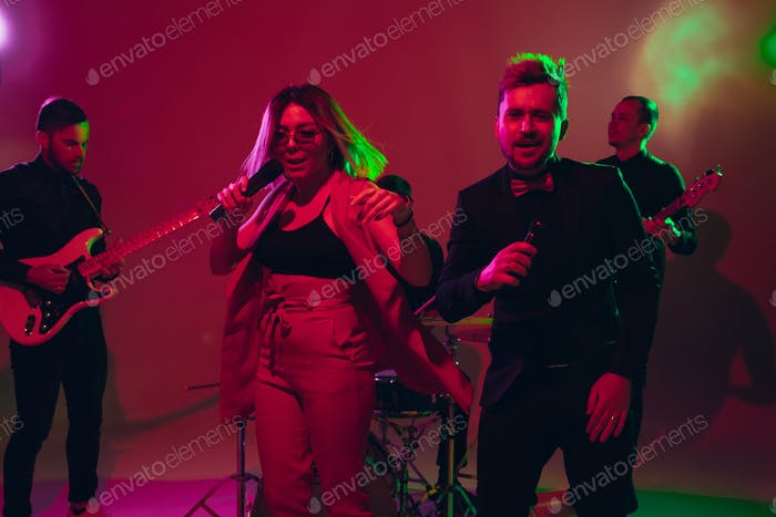 Young caucasian musicians, band performing in neon light on red studio background