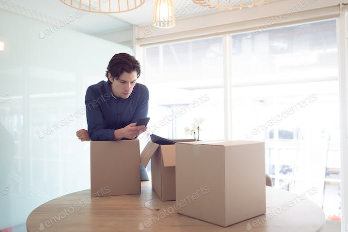 Side view of Caucasian male executive using mobile phone while leaning on cardboard box in office