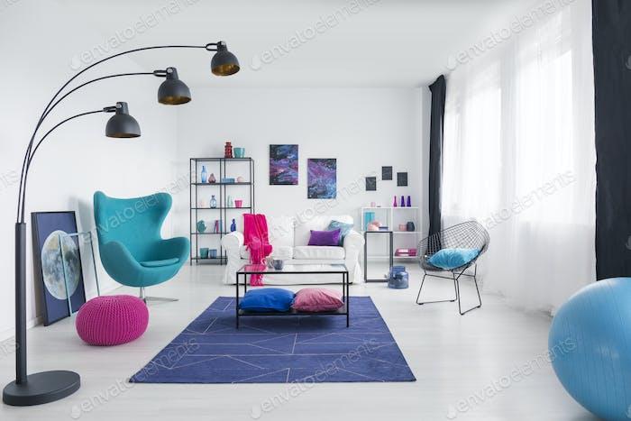 Table on blue carpet in white living room interior