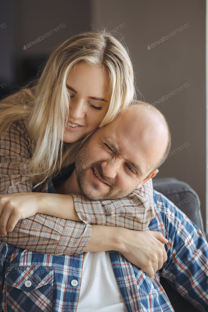 Portrait of Couple Embracing on Sofa at Home