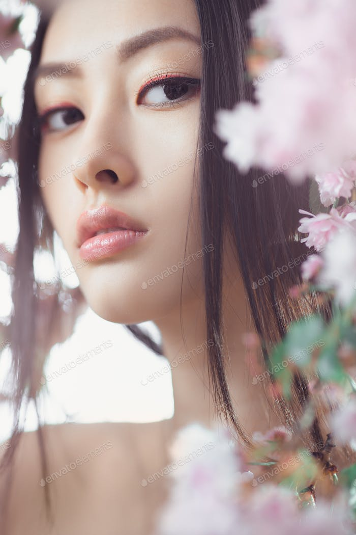 Portrait of a beautiful fantasy asian girl outdoors against natural spring flower background