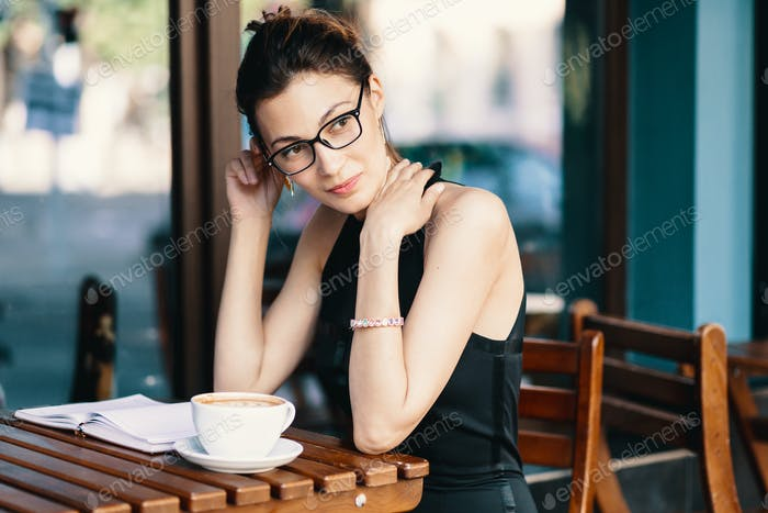 Young stylish woman with stylish glasses sitting at table in cafe with a big cup of coffee or latte
