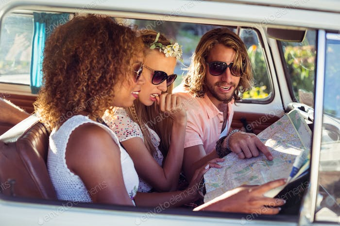 Friends looking at map in campervan