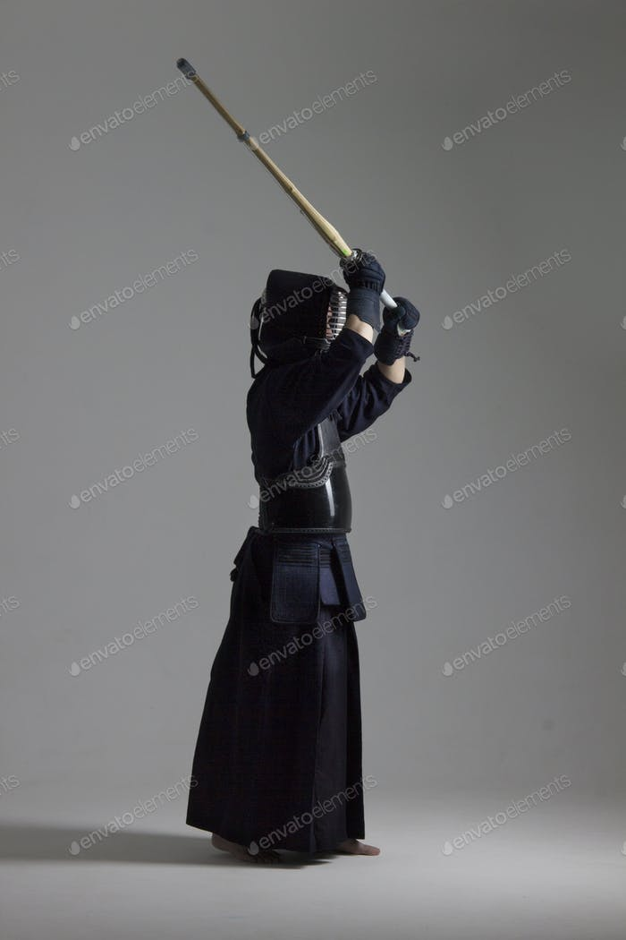 Man is practicing kendo in traditional armor .He swinging with bamboo sword