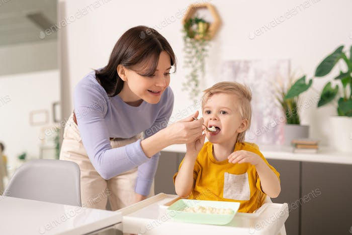 Young careful woman in casualwear helping her cute little son with breakfast