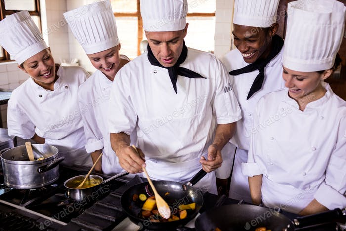 Group of chefs preparing food in kitchen at hotel