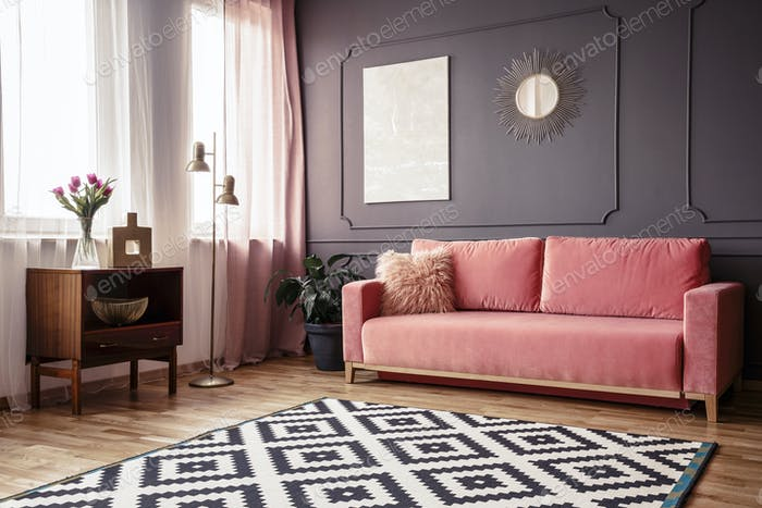 Side angle of a living room interior with a powder pink sofa, pa