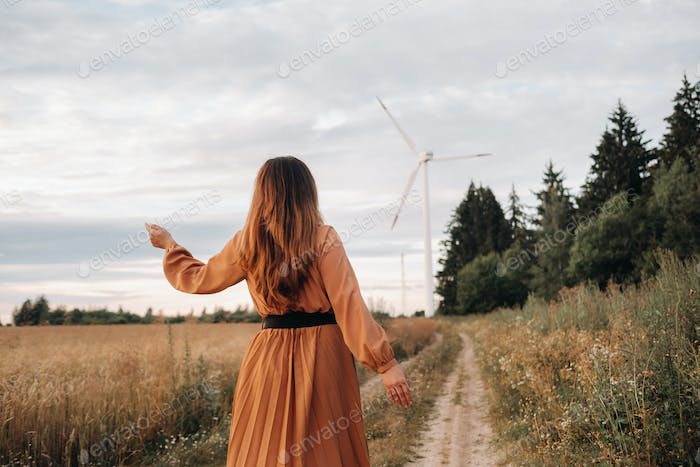 unrecognizable girl in a orangelong dress with long hair in nature in the evening against the