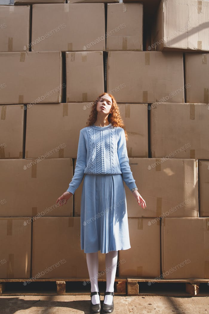 Shot of standing near boxes young woman