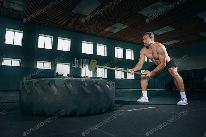 Shirtless Mann Flipping schweren Reifen im Fitnessstudio