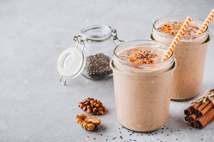 Healthy carrot and apple smoothie with walnuts and chia seeds in glass jars